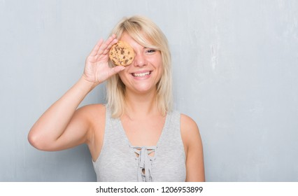 Caucasian adult woman over grey grunge wall eating chocolate cooky with a happy face standing and smiling with a confident smile showing teeth