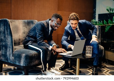 caucasian and african american businessman using laptop to discuss information in modern office