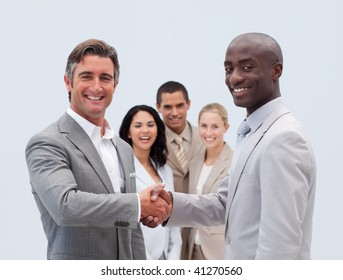 Caucasian and Afro-American businessmen shaking hands with his colleagues in the background