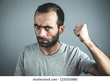 Caucasian angry man on gray background.