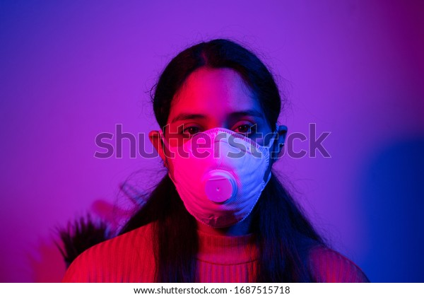 Caucasian Argentinian woman with white mask in a purple room during corona virus days looking sad