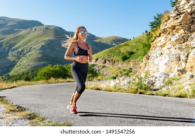Caucasian athletic woman running outdoors in the mountain on empty road.