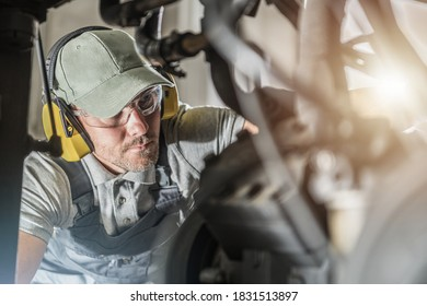 Caucasian Automotive Industry Technician in His 40s Wearing Safety Glasses Looking Into Engine Compartment To Spot Potential Issue with the Vehicle Powertrain.