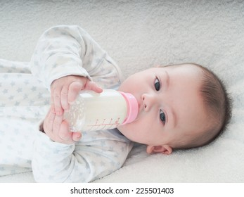 Caucasian baby boy four months drinking milk from the bottle at home