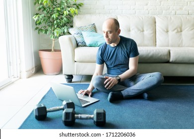 Caucasian bald man looking for some online workouts on a laptop computer and getting ready to exercise and lift some weigths at home