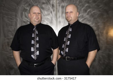 Caucasian bald mid adult identical twin standing together looking at viewer.