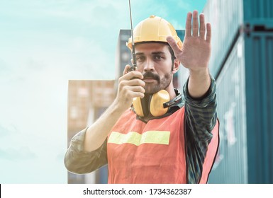 Caucasian beard foreman wearing safety helmet and making hand to stop while talking on walkie talky