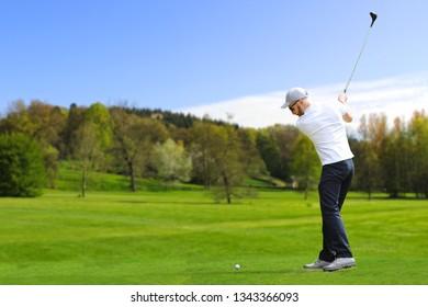 Caucasian bearded golfer hit a golf ball by golf-club driver