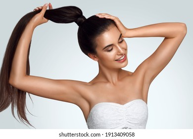 Caucasian beautiful girl holds hair in hand, raise up hands. Beauty young woman, salon body and armpit skin care, smooth armpit skin, hair removal and sugaring. Happy girl with closed eyes