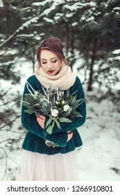 Caucasian beautiful girl outdoors. Romantic lovely toung woman with flowers in winter park. Season, fashion, beauty concept