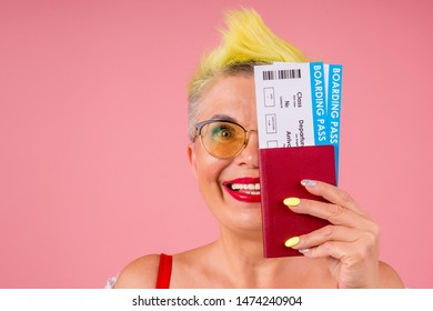 caucasian beautiful old senior with stylish yellow dyed hair and sunglasses holding passport and flight ticket on pink studio background.red lipstic forever young soul.