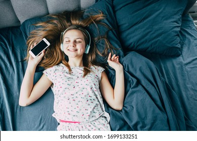 Caucasian beautiful teenager girl with long hair in pajamas lying in bed with his eyes closed and enjoying cool music in modern headphones and holding a phone. Typical teenager morning. bedding blue