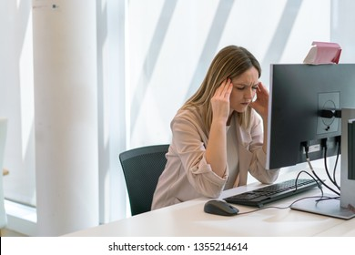 Caucasian beautiful young girl with hands on head tired and stressed from work in the office in front of computer screen