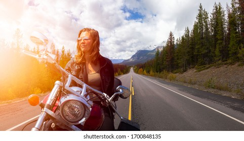 Caucasian Biker Woman on a Motorcycle on a scenic Road in the Canadian Rockies. Image Composite. Background from Banff, Alberta, Canada.