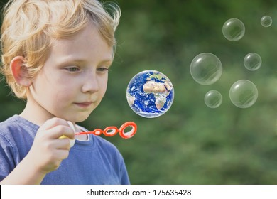 Caucasian blond boy is playing with soap bubbles. One of these bubbles is Earth globe.