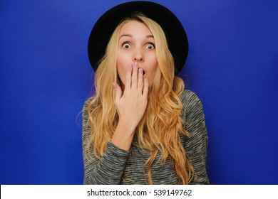 Caucasian blond girl in a black hat closes her mouth in surprise, shame, fear, horror. Blonde girl hipster in hat and gray sweatshirt on a blue background in shock from seasonal sales, big discounts.