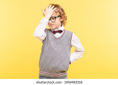 Caucasian blond kid 8-10 years old with glasses grabbed his head. Concept of vision problem, psychological, personal or educational problems, child loneliness.