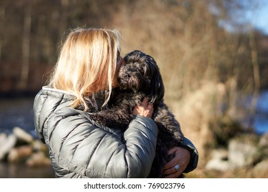 Caucasian blond woman kissing little black havanese dog