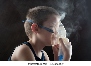 Caucasian blonde boy inhales couples containing medication to stop coughing. Medical procedures. Inhaler. Respiratory medicine. Bronchitis, asthmatic health equipment. Concept of home treatment.