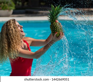 Caucasian blonde girl plays with a pineapple in the pool