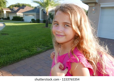 Caucasian blonde girl smiling as she walks to school wearing a pink shirt and backpack