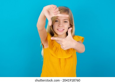 Caucasian blonde kid girl wearing yellow T-shirt against blue wall making finger frame with hands. Creativity and photography concept.
