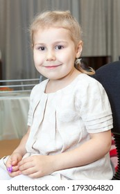 Caucasian blonde little girl with brown eyes, wearing white dress and tights, sitting on chair and looking at camera, indoor