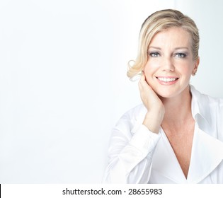 Caucasian blonde mature looking business woman in white smiles casually