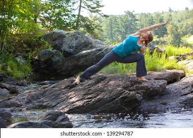 caucasian blonde middle-aged woman practicing yoga in side angle pose ion rocks beside stream, Surry, Maine, Summer