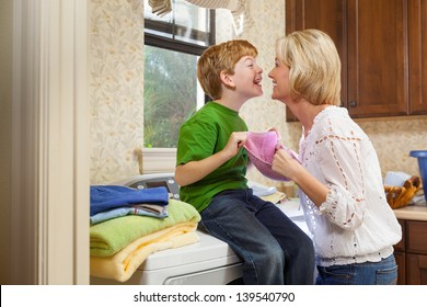 Caucasian blonde mother and red headed son doing laundry in laundry room, while looking at each other