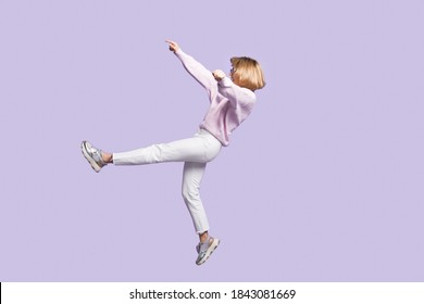 Caucasian blonde woman is gesturing a falling on a violet studio wall wearing glasses and stylish clothes