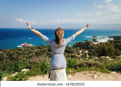 A caucasian blonde woman in a striped dress sits on a hill with her arms wide apart and looks at the sea, trees and mountains. Space for text