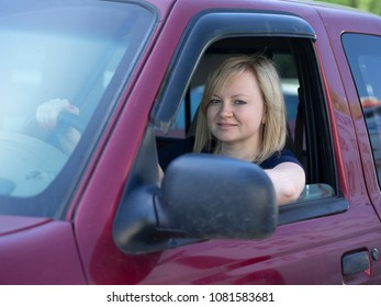 Caucasian blonde young woman driving in the cab of a red pickup truck