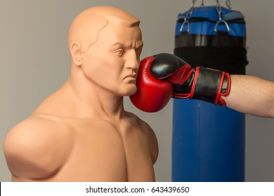 Caucasian boxer wearing red boxing gloves punching straight on a dummy mannequin doll on a gym with a blue punching bag on the background
