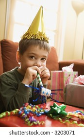 Caucasian boy at  birthday party looking at viewer blowing noisemaker.