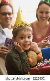 Caucasian boy at  birthday party looking at viewer making facial expression.