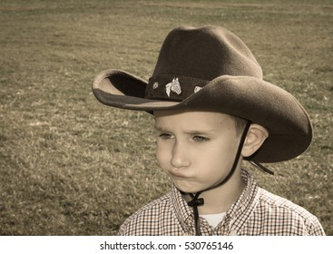 Caucasian boy with cowboy hat, smirking and thinking face, and space for text