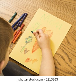 Caucasian boy drawing on paper with crayons.