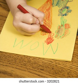 Caucasian boy drawing on yellow paper with crayons.