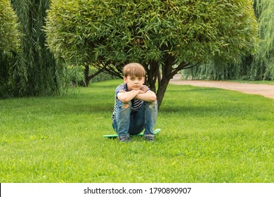 Caucasian boy dressed casual sits on skateboard in park on grass