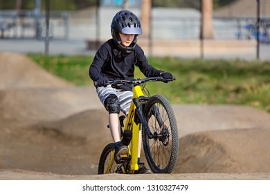 caucasian boy in full face helmet enjoying downhill mountain biking, extreme sports concept
