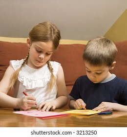 Caucasian boy and girl drawing on paper with crayons.