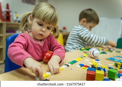 Caucasian boy and girl playing with wooden toy in kindergarten