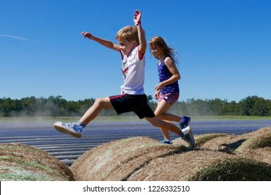 Caucasian boy and girl running and jumping on top of haystacks on a farm