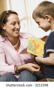 Caucasian boy giving mid adult mother a drawing.