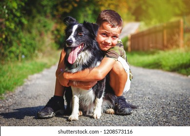 Caucasian boy with his dog outdoors. Cute boy hugs his border collie on the road.