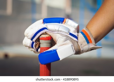 Caucasian boy holding cricket bat wearing blue and white colored glove.
