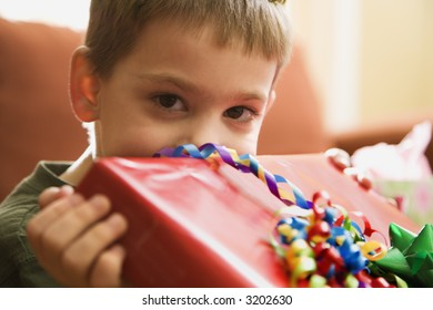 Caucasian boy holding gift up to face and looking at viewer.