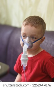 Caucasian boy inhales couples containing medication to stop coughing. Medical procedures. Inhaler. Respiratory medicine. Bronchitis, asthmatic health equipment. Concept of home treatment.