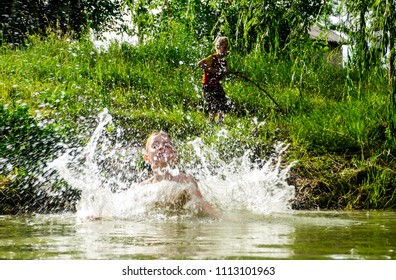 Caucasian boy jumping into the water in a pond, raising splashes